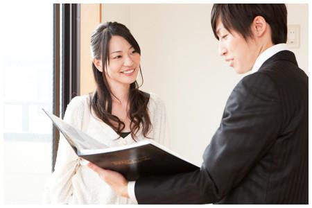 ファイルを開いて説明するスーツの男性と聞く女性